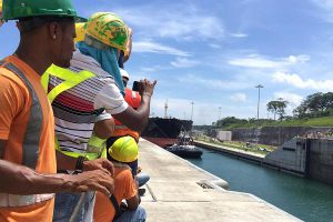 Justin Solomon | CNBC Hundreds of construction workers lined the sides of the new lane of the Panama Canal to watch the first ship, a post-Panamax ship pass through.