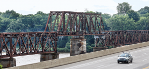 Derided by some as a blight, but also eligible for listing on the National Register of Historic Places, a trackless former railroad bridge next to the Ohio Turnpike's Maumee River bridge is to be torn down next year.